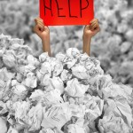 Hands with red help sign reaches out from big heap of crumpled papers