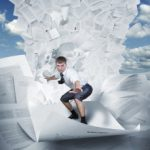 Extreme project management - a person surfing down a mountain of papers