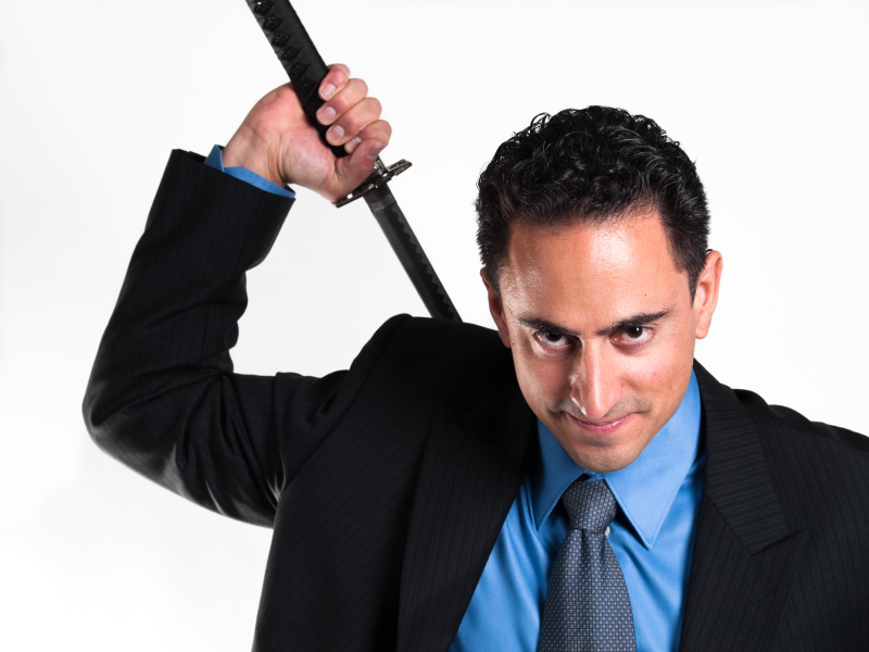 Suited man wielding a Samuri sword over his shoulder