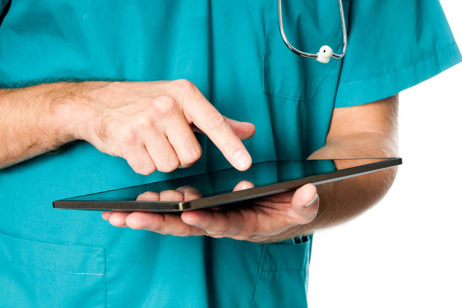 Torso of a person in scrubs holding an ipad