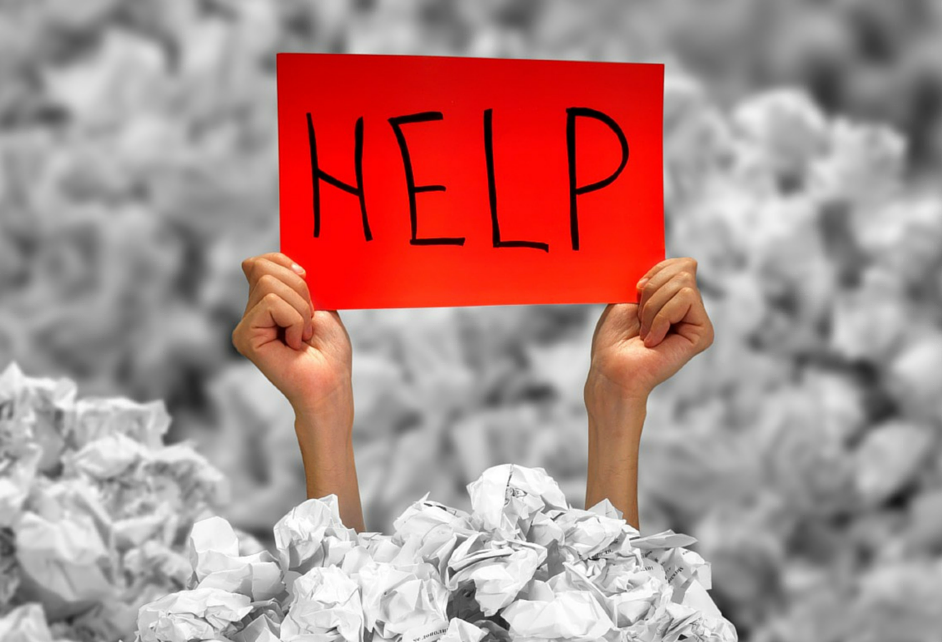 Hands holding a help sign in a sea of crumpled paper