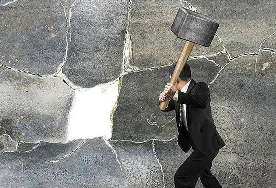 Suited man smashing a wall with a hammer